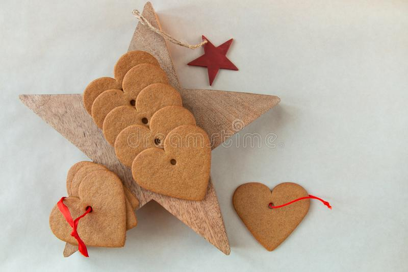 Christmas heart shaped gingerbread cookies on wooden star royalty free stock images