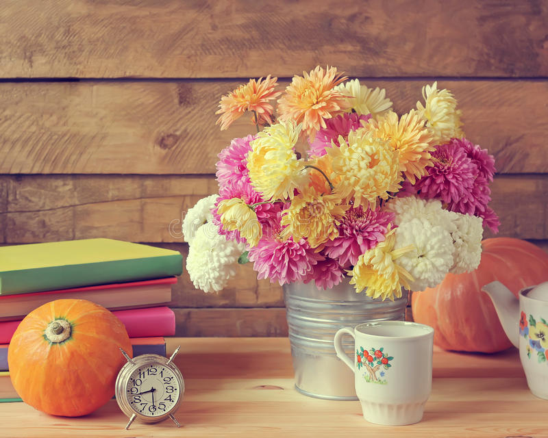 Still life with chrysanthemums, pumpkins, ware, books and an ala stock photo