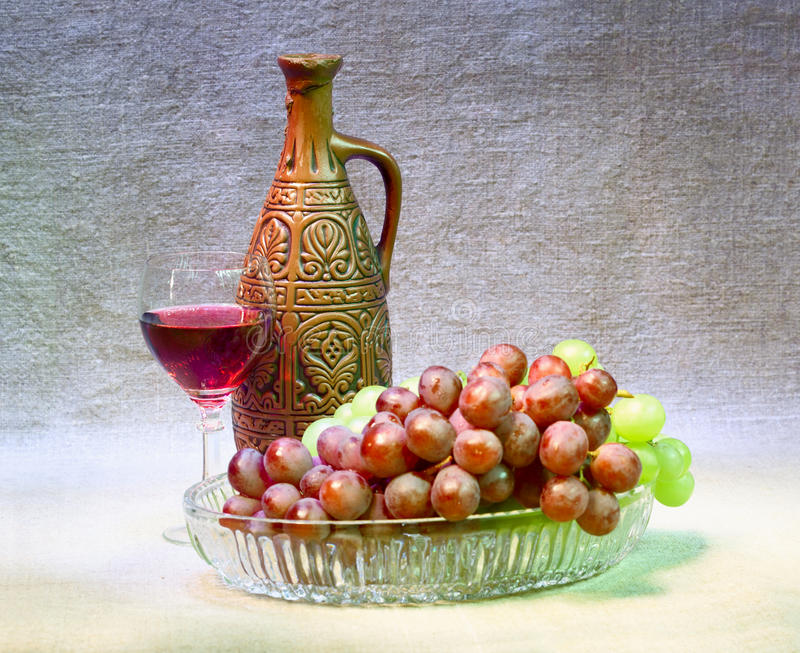Still-life with clay bottle, grapes and glass. Still-life with a clay bottle, grapes and a glass on a canvas background stock image