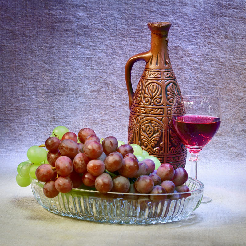 Still-life with clay bottle, grapes and glass. Still-life with a clay bottle, grapes and a glass royalty free stock photos