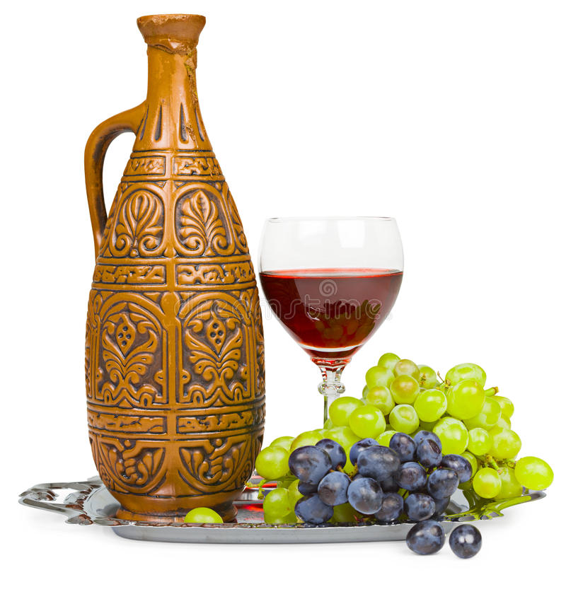 Still life - clay jug, glass of wine and grapes. Still life - a clay jug, a glass of wine and grapes isolated on white stock photography