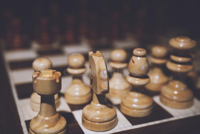 Still life close up detail view of a queen chess dark wooden piece on a chess board while a strategic game is being played. Interi royalty free stock images