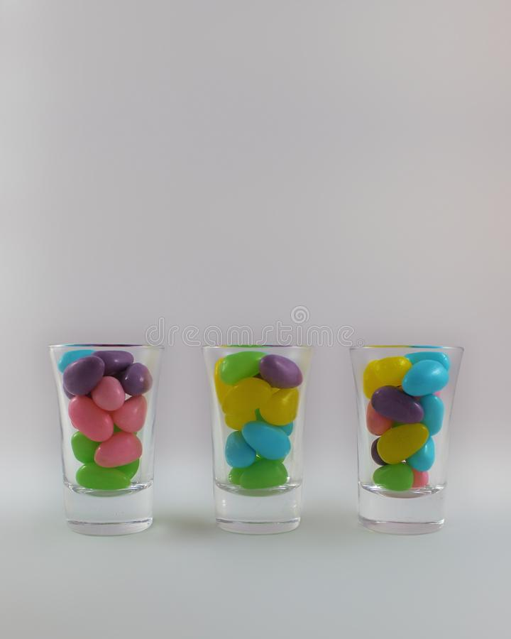 Bar shot glasses filled with colorful jelly beans isolated on light gray background with copy space royalty free stock images