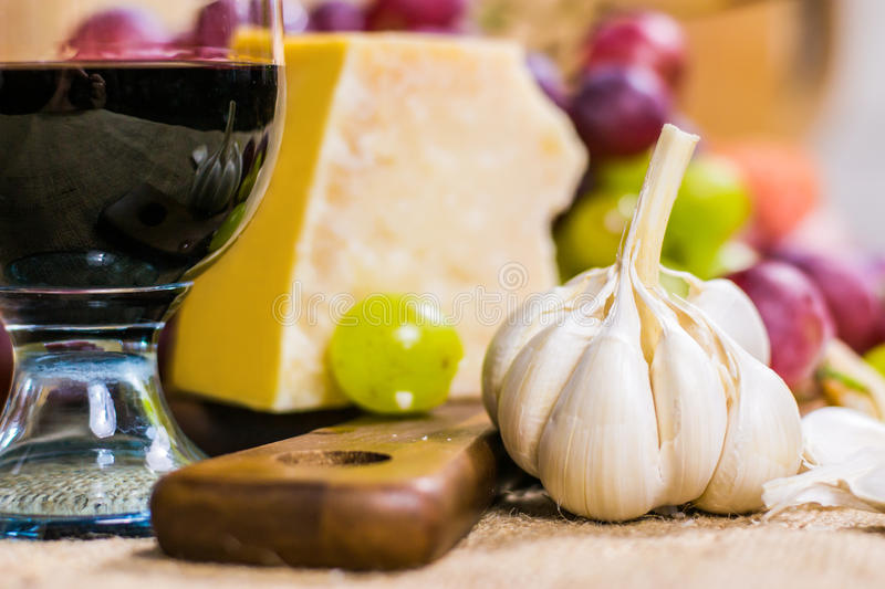 Still life - close up view of yellow and red muscat grape, cheese, garlic and a glass of wine on a wooden board and canvas stock photo