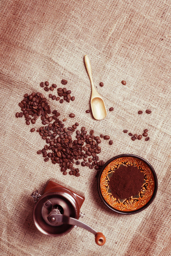 Still life with coffee beans, coffee mill, cup and a wooden spoon stock photography