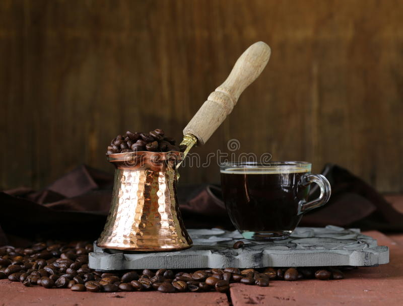 Still life coffee cup espresso beans and coffee pot. On a wooden table stock photo
