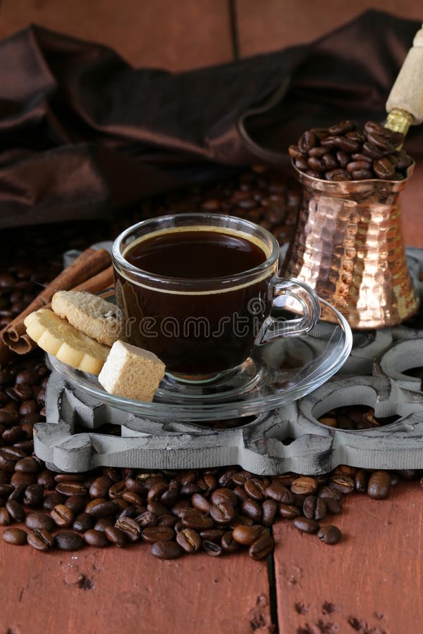Still life coffee cup espresso beans and coffee pot. On a wooden table royalty free stock image