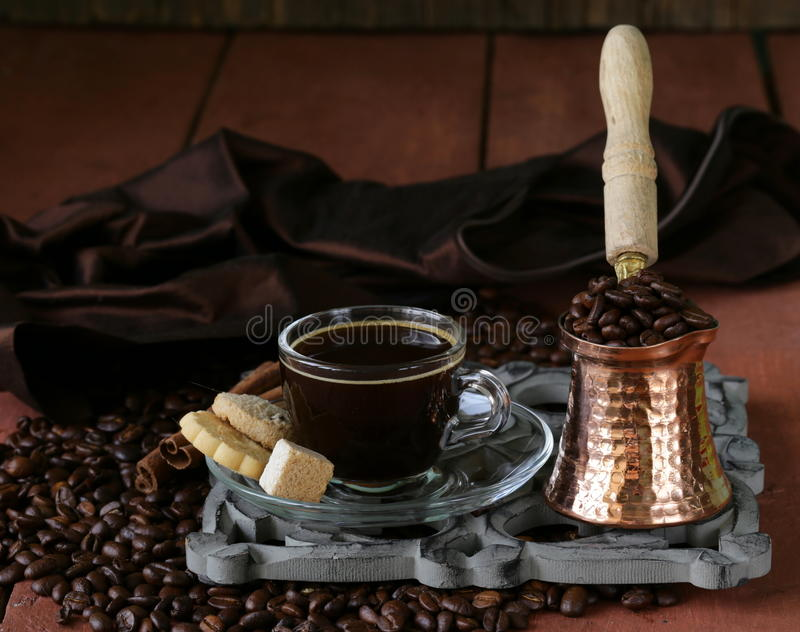 Still life coffee cup espresso beans and coffee pot. On a wooden table stock photography