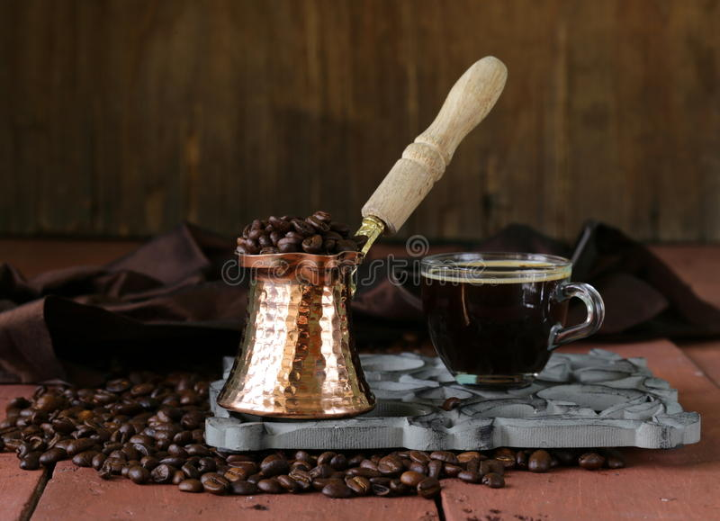 Still life coffee cup espresso beans and coffee pot. On a wooden table royalty free stock images