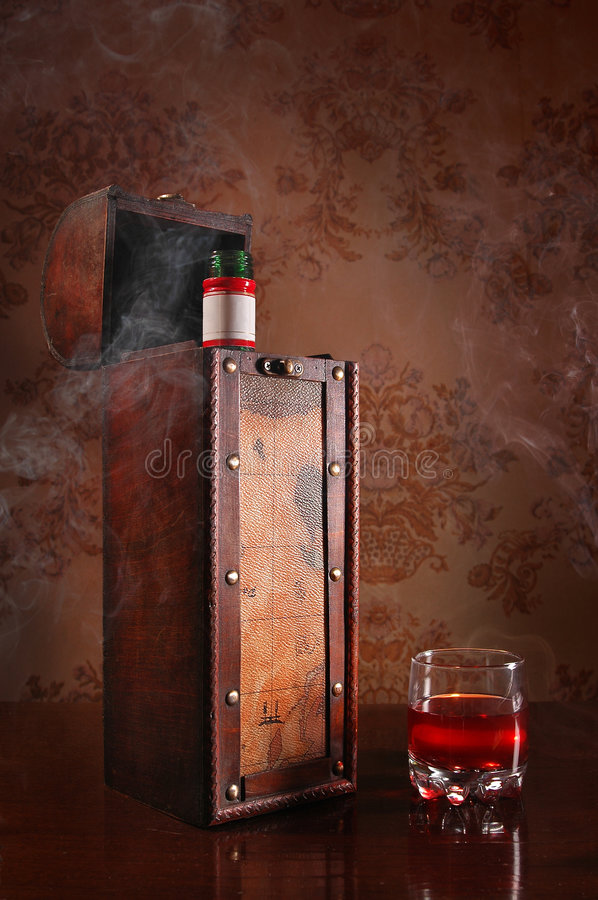 Still life with cognac glass and bottle. In box royalty free stock photography