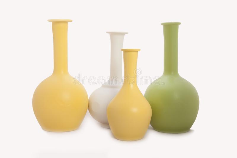 Still life with colorful monochromatic vases on a white background stock image