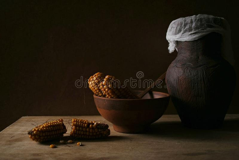 Still life with corn and a clay jug royalty free stock photo