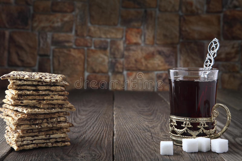 Still life with a cracker and black tea in a glass with a retro cup holder and three slices of sugar. Retro stylized photo. Close- stock photos