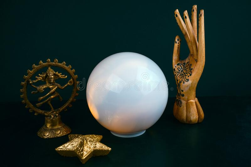 Still life with a crystal ball and wooden hand, statuette of the God Shiva on a black background. Esoteric still life with a crystal ball and wooden hand royalty free stock photo