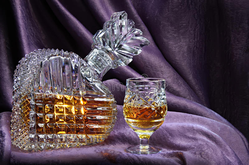 Still life with a crystal decanter and glass. Carafe and glass stock photo
