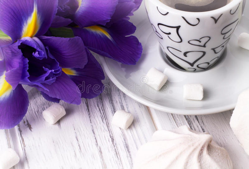 Still life with cup of coffe marshmallow iris flowers purple ribbon on white wooden background. Wedding. Valentines Day. Womans Da royalty free stock photo