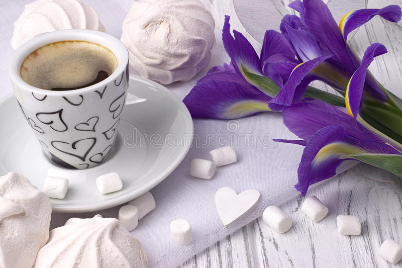 Still life with cup of coffe marshmallow zephyr iris flowers heart sign on white wooden background. Wedding. Valentines Day. Woman stock photo