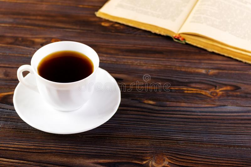 Still life with cup of coffee and book on grunge wood table in vintage style stock photo