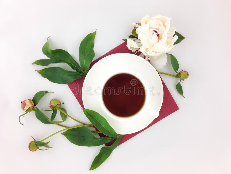 Still life with cup of coffee and peony flowers on white table. Flat lay, top view stock images
