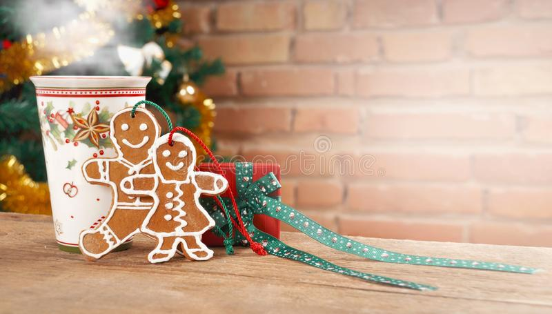 Still life with cup of hot drink and gingerbread man on brick background. Still life with cup of hot drink, red gif box and gingerbread man on wooden table and stock images