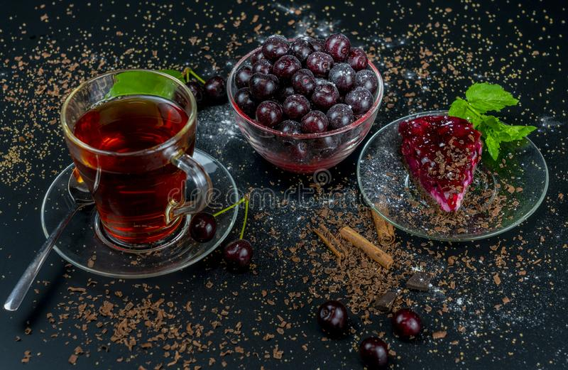 Still life with a Cup of strong tea, ripe cherries and cherry cake on a black background.  royalty free stock photography
