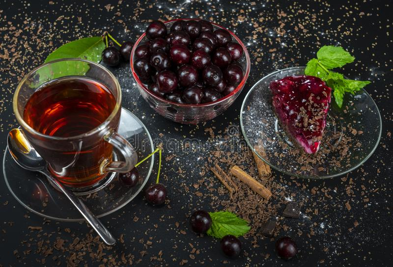 Still life with a Cup of strong tea, ripe cherries and cherry cake on a black background.  stock image