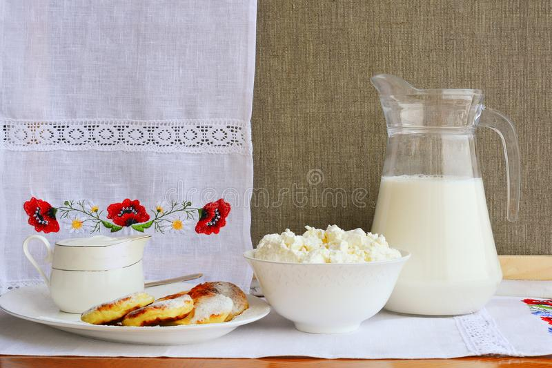 Still life of dairy products on a background of a towel with embroidery ..of red poppies. Cheesecake, home cottage cheese, milk i stock photos