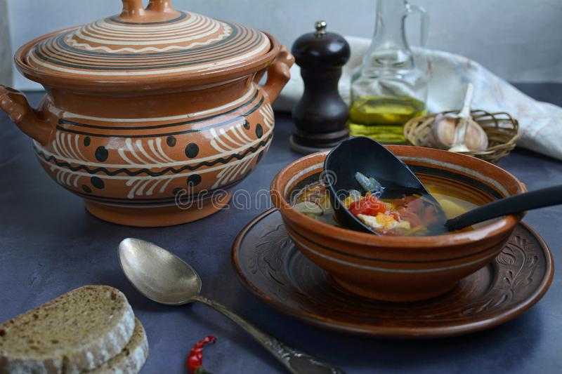 Still life on a dark table from a ceramic bowl, plates with vegetable soup, bread, spoon and seasonings stock photography