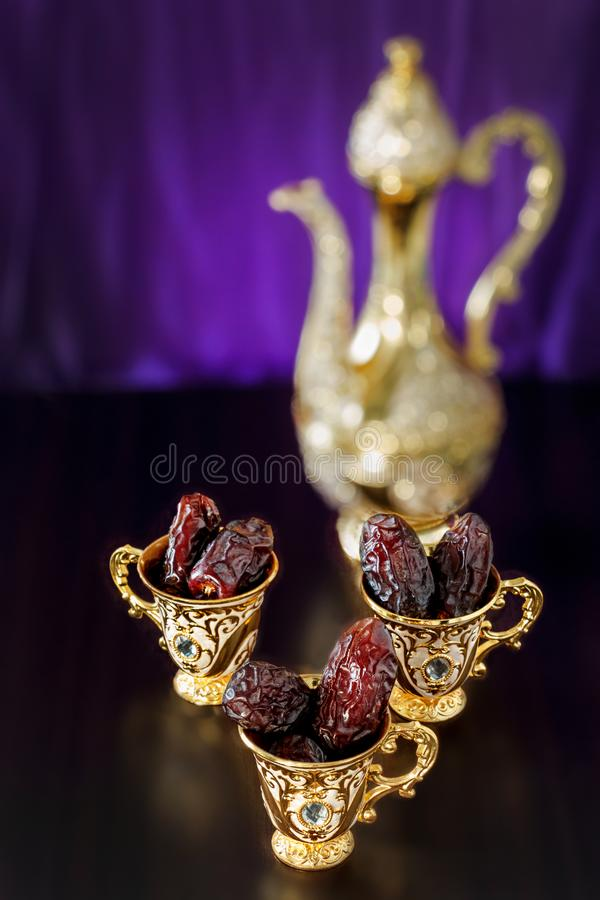 Still life with dates with golden Traditional Arabic coffee set with dallah and mini cup. Dark background. royalty free stock photo