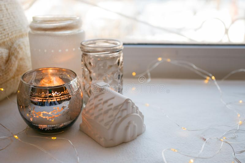 Still life details with candles, toy house and garland. Scandinavian hygge concept, monochrome, kinfolk style. Still life details with candles, toy house and royalty free stock images