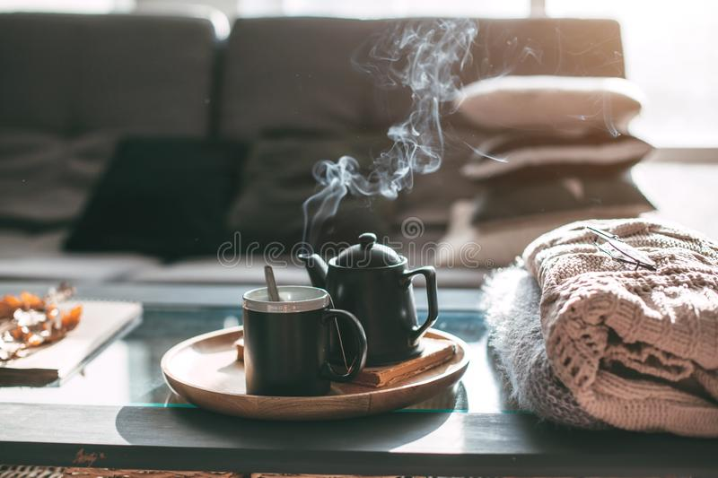Tea with steam in room in morning sunlight. Still life details in home interior of living room. Sweaters and cup of tea with steam on a serving tray on a coffee stock image