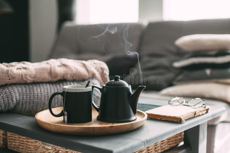 Tea with steam in room in morning sunlight. Still life details in home interior of living room. Sweaters and cup of tea with steam on a serving tray on a coffee stock images