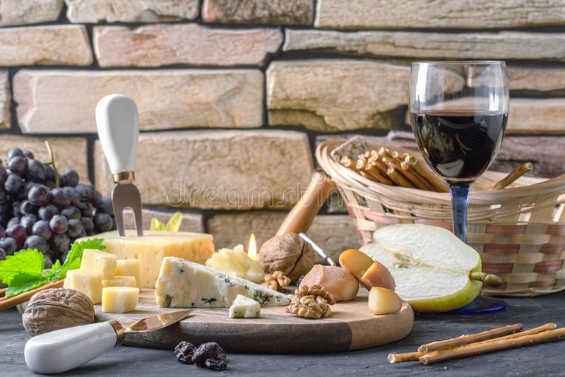 Still life with different varieties of cheese on wooden plate. Nuts, bread sticks, grapes, raisins, wine corkscrew and glass of wine royalty free stock images