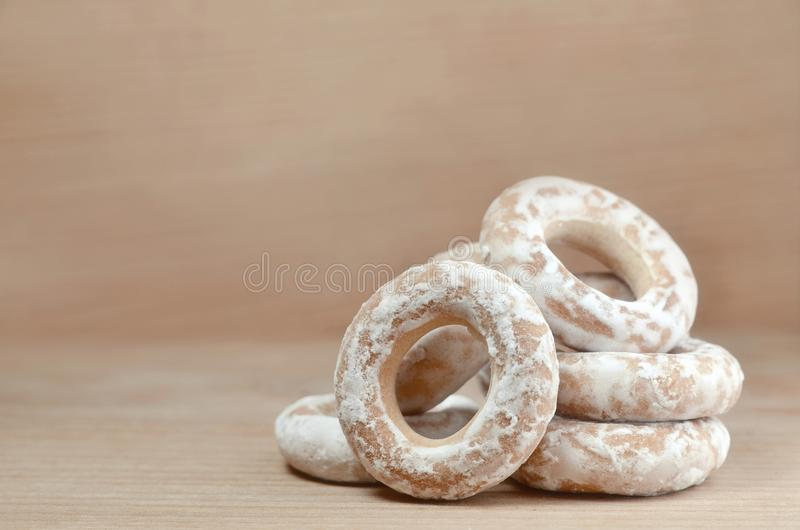 Still life of donut glaze on a wooden surface. Glazed bagels are a small bunch on a wooden table. Flour sweets to the Tea Part royalty free stock photography