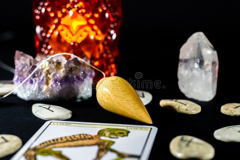 Still Life With Dowsing Pendulum. A dowsing pendulum among runes with a tarot card stock image