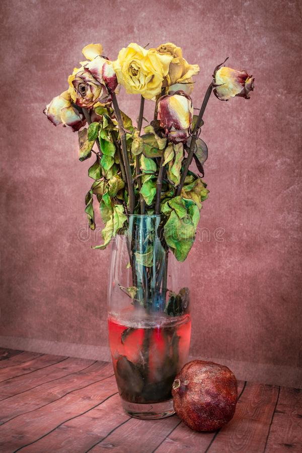 Still life of dry flowers in a vase with the water with pomegranate royalty free stock photos