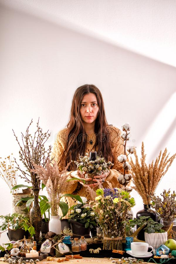 Still life with dry flowers and willow branches on a wooden table. Decor candles, dry branches of willow and a girl on the royalty free stock image