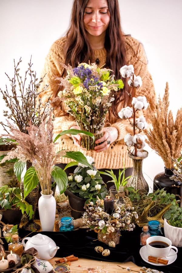 Still life with dry flowers and willow branches on a wooden table. Decor. decorations, dry branches of willow and a girl on the stock photo