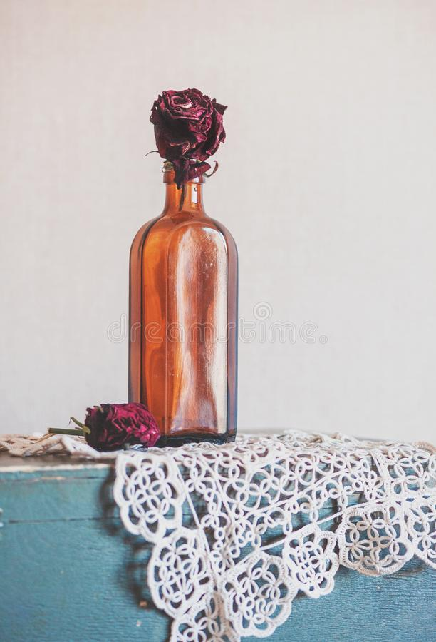 Still life with dry red roses in glass bottle on the vintage lac. E fabric and old wood stock images