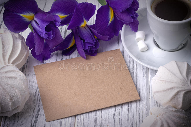 Still life with envelop coffee cup marshmallows iris flowers on white wooden background. Wedding. Valentines Day concept. royalty free stock photo
