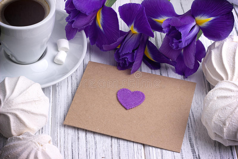 Still life with envelop heart sign iris flowers on white wooden background. Wedding. stock photography