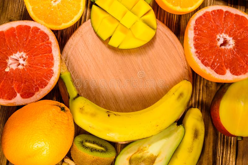 Still life with exotic fruits and cutting board. Bananas, mango, oranges, avocado, grapefruit and kiwi fruits on wooden table. Top. Still life with exotic fruits stock images