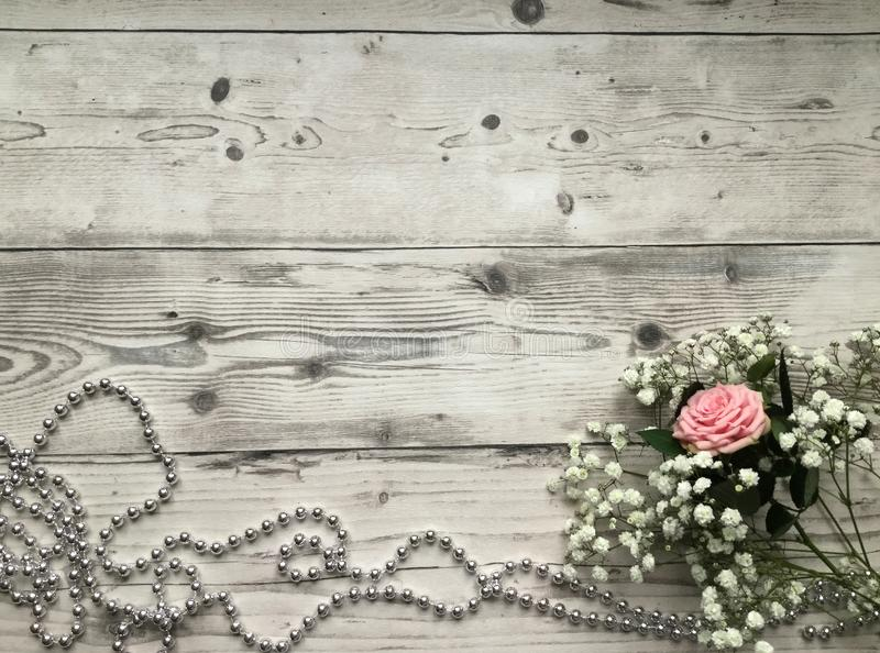 A still life flat lay concept on the light wooden background, white flowers and a pink rose accompanied with silver pearls stock image
