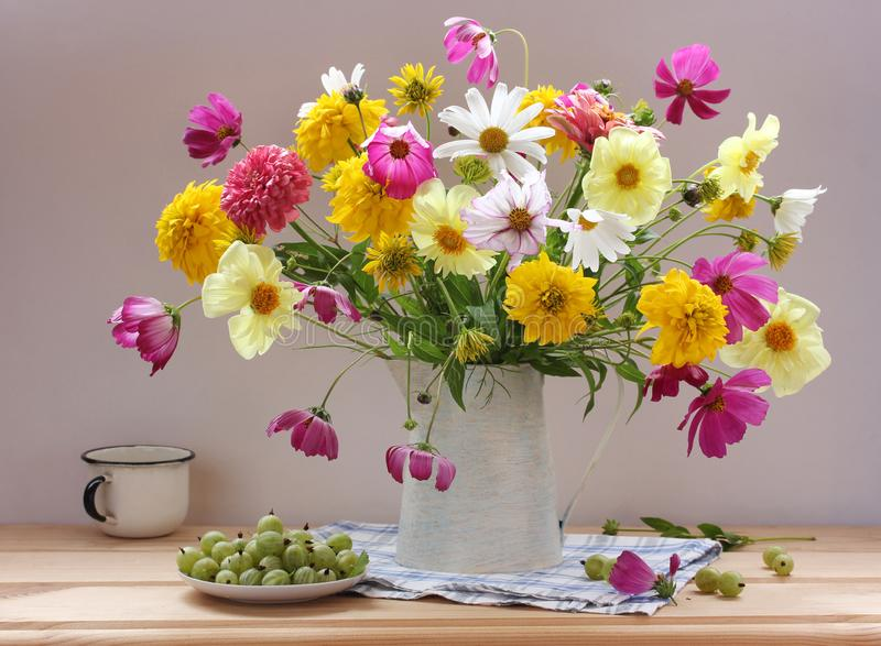 Still life with flowers and berries on the table. Garden bouquet and green gooseberry royalty free stock photos