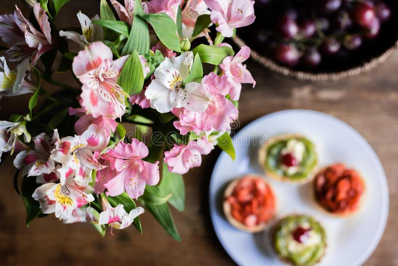 Still life of flowers, breakfast with cakes and fruits royalty free stock photos