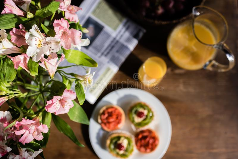 Still life of flowers, newspaper, breakfast with cakes and glass of juice stock photography