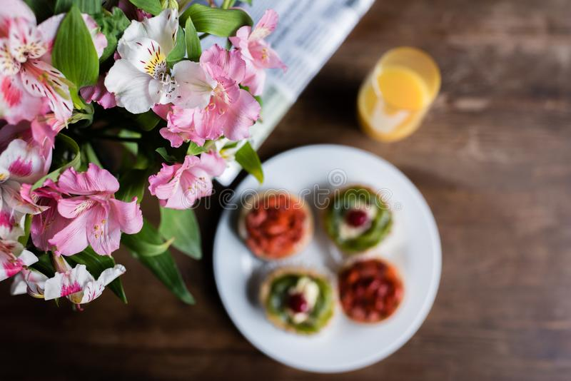 Still life of flowers, newspaper, breakfast with cakes and glass of juice royalty free stock photography