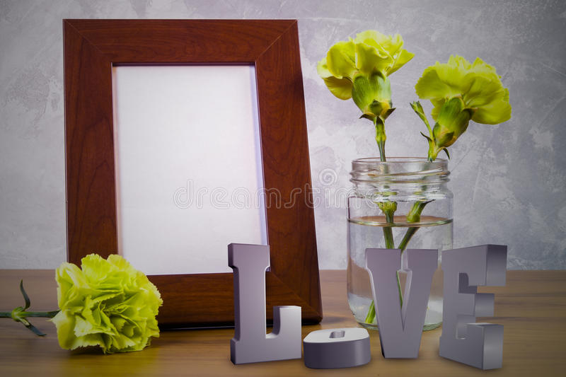 Still life with flowers and white photo frame on wooden table ov. Er grunge background. Valentine concept royalty free stock photo