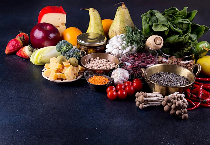 Still life food set on dark background. Concept healthy eating. Broccoli, chicory, beans, lentils, chili, nut, cheese, garlic, spi stock images