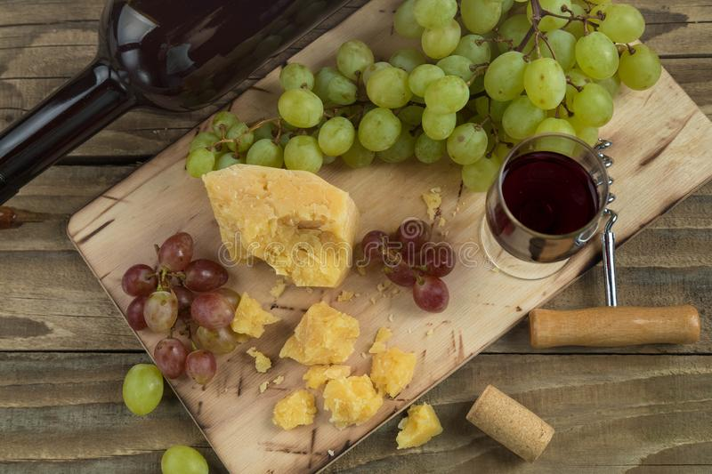 Still life from food and wine. The piece of hard cheese lies on a chopping board. Clusters of red and green mature grapes, a dark royalty free stock photography